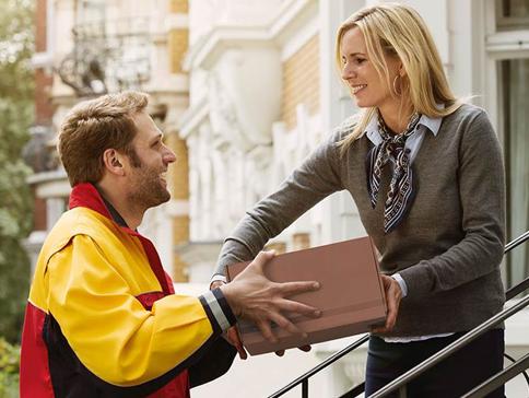 Bezorging van een pakket door koerier aan een vrouw